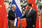 Президент России Владимир Путин (слева) и его китайский коллега Си Цзиньпин пожимают друг другу руки, архивное фото