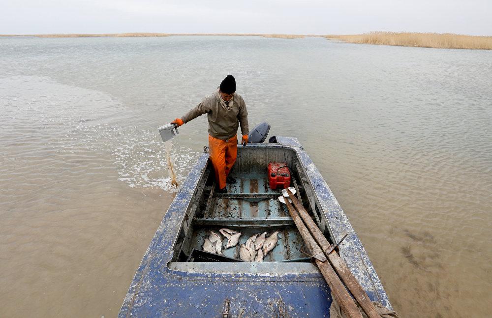 Рыбак вычерпывает воду из своей лодки на берегу Аральского моря, архивное фото