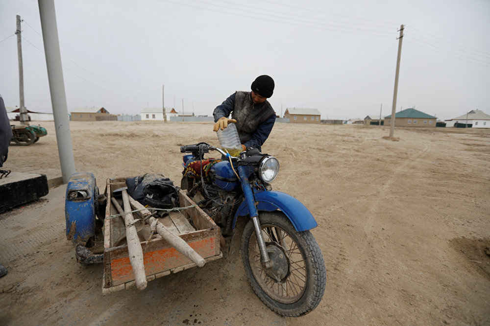 Рыбак заправляет свой мотоцикл в деревне вблизи Аральского моря, архивное фото