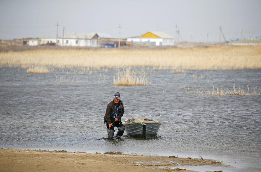 Сельский житель привязывает лодку на берегу Аральского моря, архивное фото