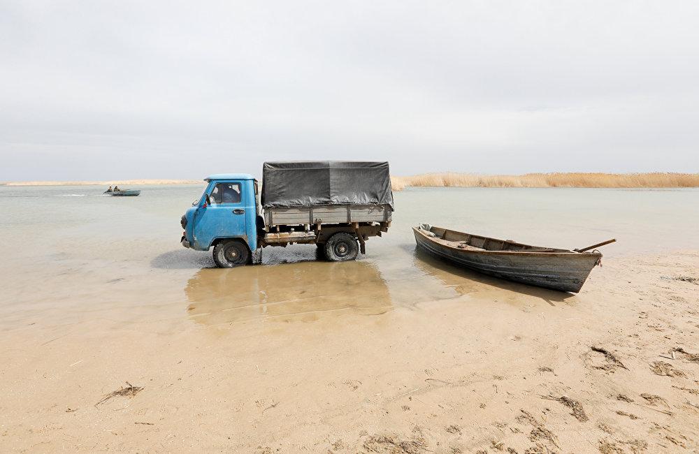 Рыбаки на грузовике  собирают рыбу с лодки на мелководье по Аральскому морю