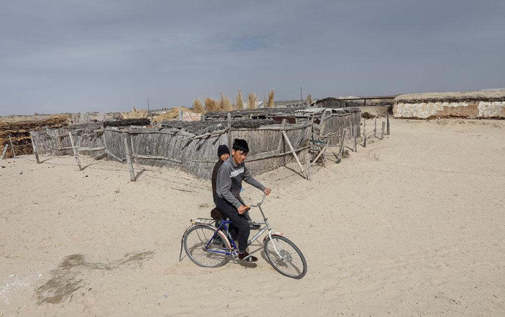 Мальчик едет на велосипеде в деревне вблизи Аральского моря
