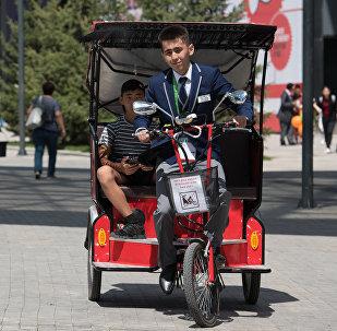 Велорикша на выставке ЭКСПО катает детей