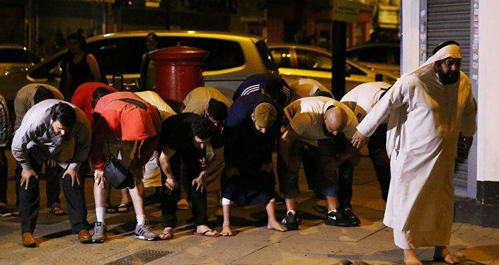 Мужчины молятся после наезда фургона на людей в Лондоне