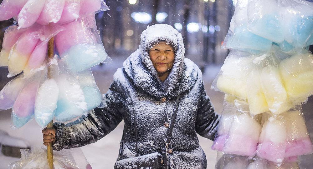 Продавщица сладкой ваты во время метели в городе Бишкек