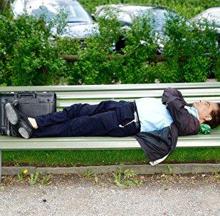 Мужчина  отдыхает в парке на скамейке