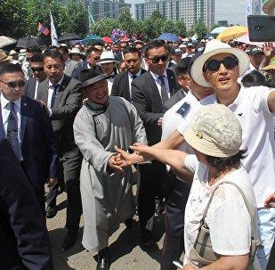 Халтмаагийн Баттулга (в центре) пожимает руку женщине