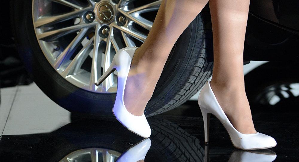 Девушка стоит рядом с автомобилем марки Lexus, архивное фото
