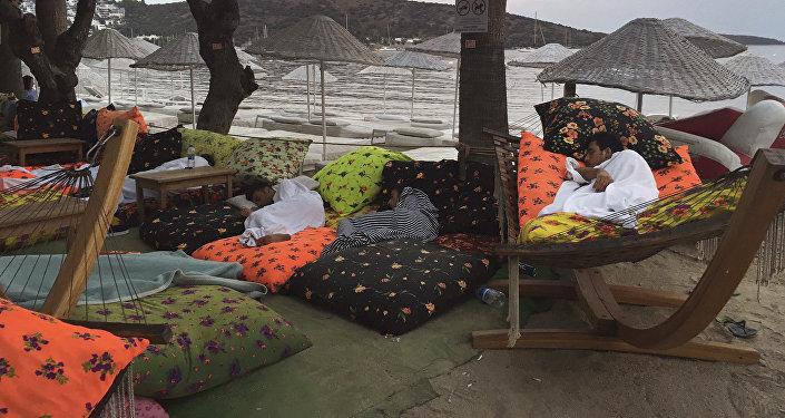 Люди спят на пляже, проведя ночь на свежем воздухе после землетрясения в Битез, курортном городе, расположенном примерно в 6 км к западу от Бодрума, Турция, в пятницу, 21 июля 2017 года