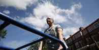 Пожилая женщина занимается спортом во дворе дома, архивное фото