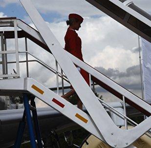 Стюардесса спускается по трапу самолета, архивное фото