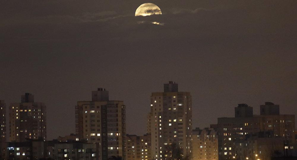 Луна поднимается из-за жилых домов, архивное фото
