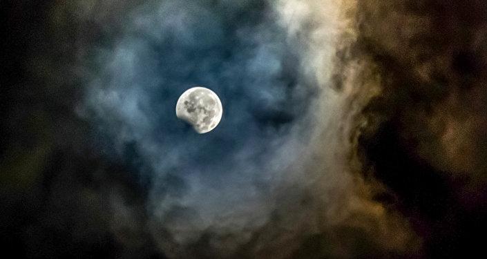 Луна, обрамленная пеплом от вулкана Маунт Синабунг, видна во время пика пунмбрального затмения из Каро в провинции Северная Суматра 8 августа 2017 года