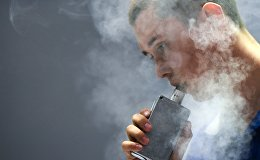 Мужчина курит вейпер, архивное фото