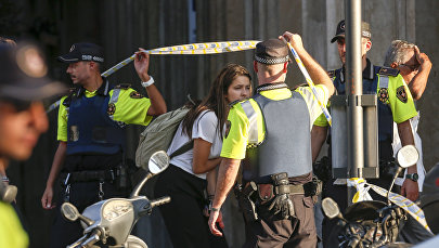 Девушка покидает оцепленную зону после того, как фургон въехал в толпу в центре Барселоны