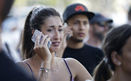 Люди говорят по телефону после того, как фургон вхъехал в толпу людей в центре Барселоны
