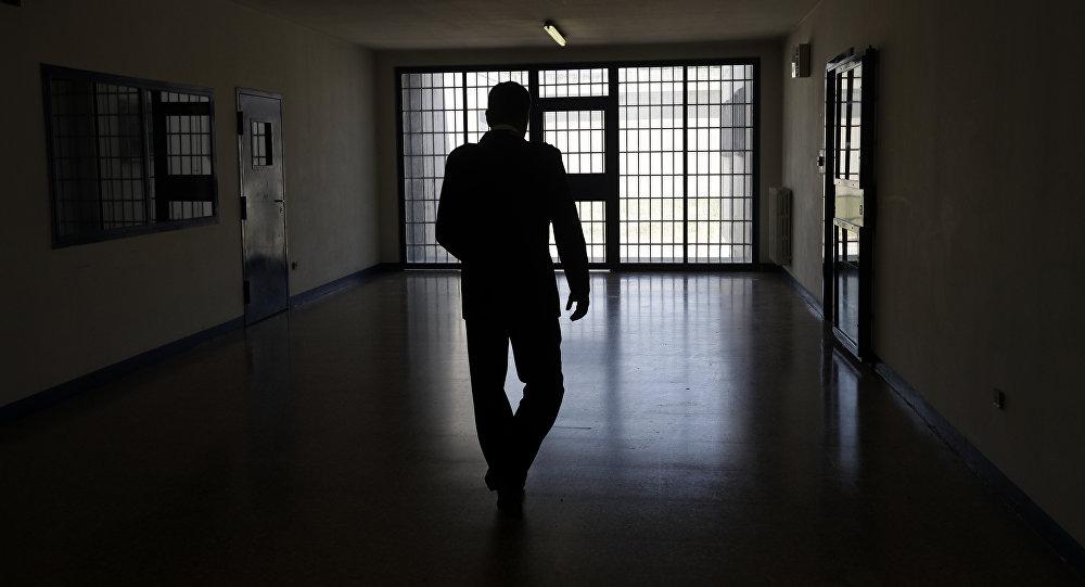 Мужчина на фоне тюремной решетки, архивное фото