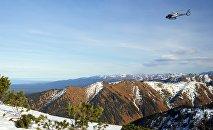 Вертолет пролетает над горами, архивное фото