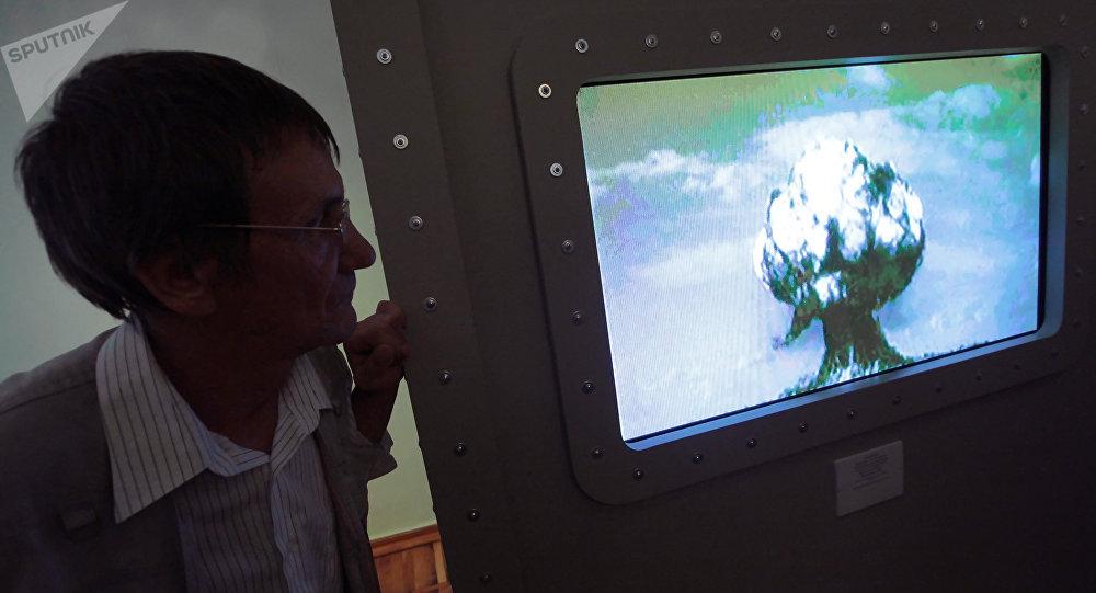Женщина смотрит архивное видео ядерного взрыва