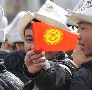 Ер адам қолында Қырғызстан туын ұстап тұр, архив суреті