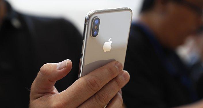 Ер адам iPhone X ұстап отыр