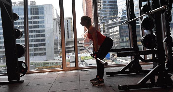 Девушка занимается в фитнес-клубе