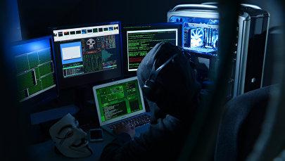 Хакер за монитором компьютера, иллюстративное фото