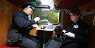 Сотрудники пограничной службы проверяет документы у пассажиров поезда на пункте пропуска железнодорожной станции , архивное фото