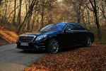 Автомобиль на дороге, усыпанной осенними листьями