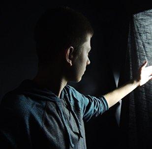 Подросток смотрит в окно