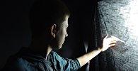 Парень смотрит в окно, иллюстративное фото