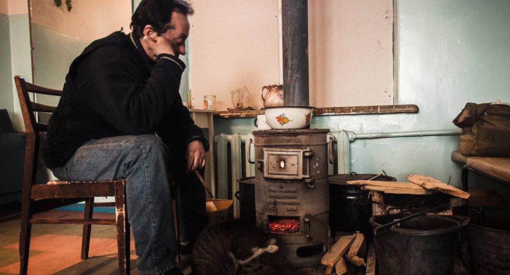 Мужчина сидит у растопленной печи, архивное фото