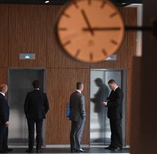 Офисные сотрудники стоят у лифта, архивное фото
