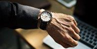 Мужчина смотрит на часы, архивное фото