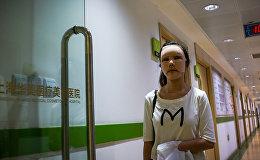 Девушка выходит из клиники пластической хирургии, архивное фото