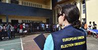 Наблюдатель за выборами в Европейском союзе находится около людей, которые находятся на избирательном участке, архивное фото