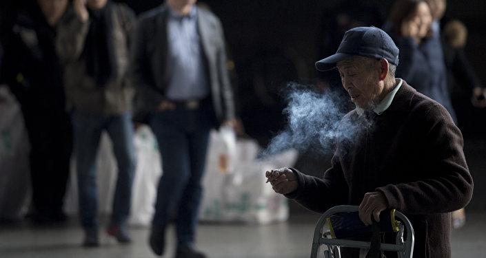 Мужчина курит на железнодорожной станции в Шанхае, архивное фото