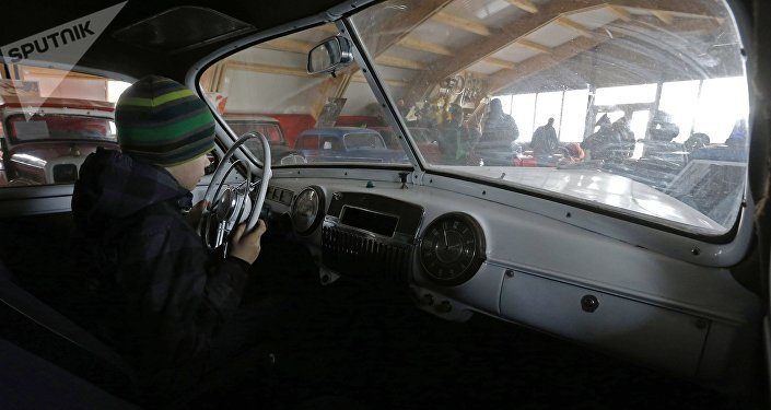 Мальчик сидит за рулем ретро-автомобиля, архивное фото