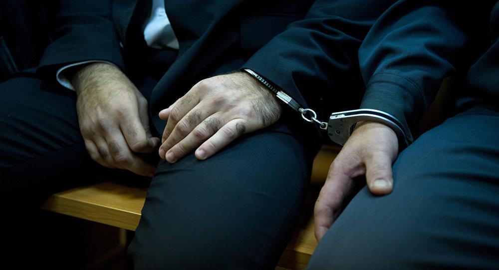 Архивное фото людей в наручниках в клетке для подсудимых