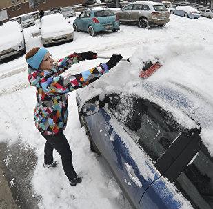 Женщина чистит машину от снега