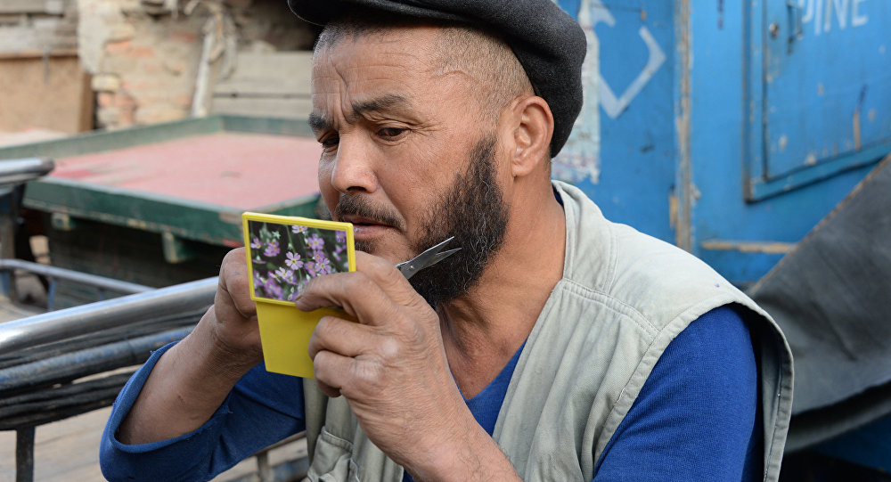 Мужчина стрижет бороду