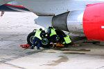 Техники во время работ с шасси в аэропорту, архивное фото