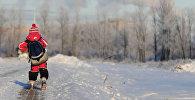 Школьник идет по заснеженной улице, архивное фото