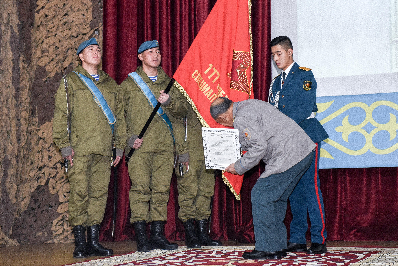 Борис Керимбаев целует знамя отряда спецназа