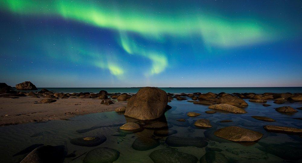 Северное сияние в небе над пляжем Уттаклейв на Лофотенских островах, Полярный круг