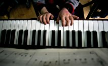 Ребенок играет на пианино, архивное фото