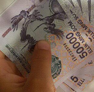 Человек держит в руках купюры номиналом 50 тысяч узбекских сум, иллюстративное фото