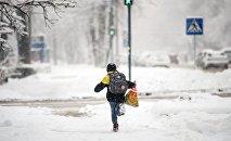 Школьник бежит по зимней дороге, архивное фото