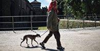Местная жительница прогуливется с собакой у замка Сфорца в городе Милане