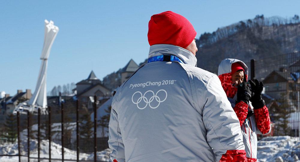 Волонтеры с изображением логотипа Олимпиады в Пхенчхане на куртке